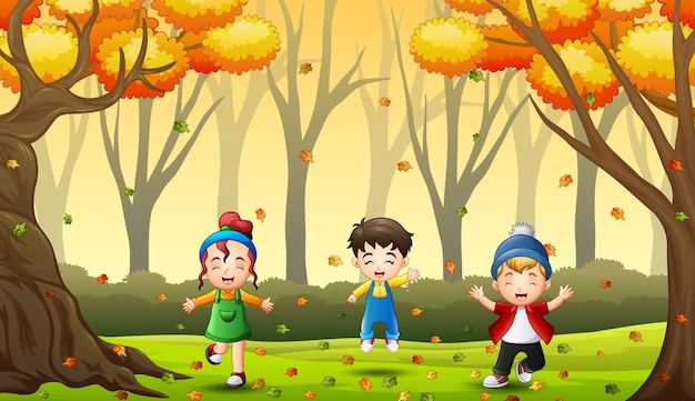 Happy kids having fun and playing with autumn leaves in forest