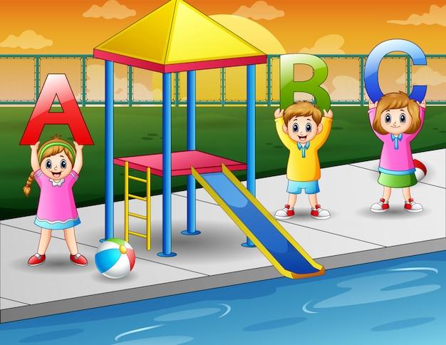 수영장에서 abc 편지를 들고 행복한 아이들