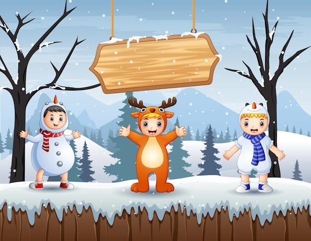 눈 덮인 숲 풍경에 동물 의상을 입은 행복한 아이들
