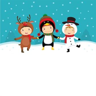 Счастливые дети в рождественских костюмах играют со снегом