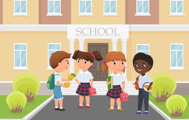 Счастливые дети перед входом в здание школы, смешная разнообразная группа студентов, стоящих
