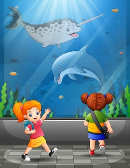 Happy kids looking at ocean fishes aquarium