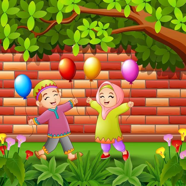 Happy kids muslim cartoon holding balloon under trees