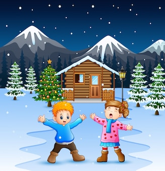 Happy kids playing in front of the snowing wooden house