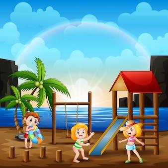 Счастливые дети играют на детской площадке рядом с пляжем