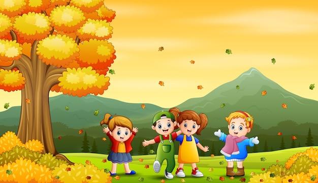 Счастливые дети, играющие на открытом воздухе осенью