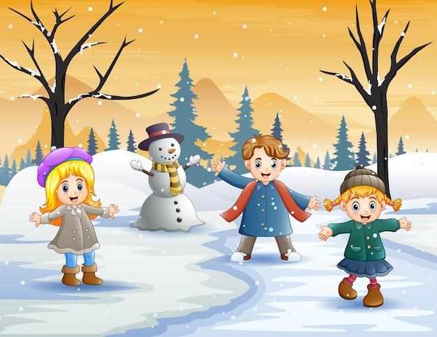 冬に屋外で遊ぶ幸せな子供たち
