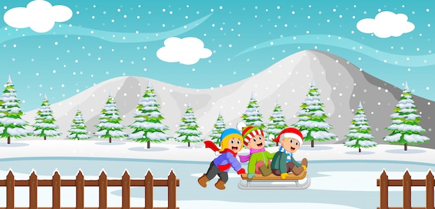 Happy kids playing a sleigh ride in winter with mountain background