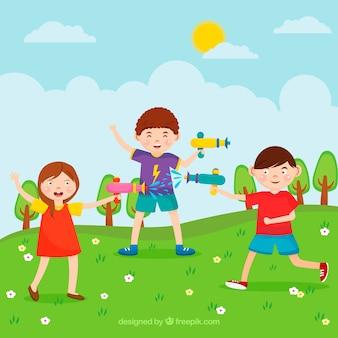 公園の水の銃で遊んでいる幸せな子供たち