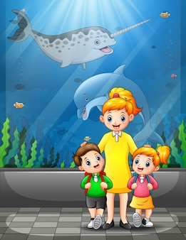 Happy kids visiting an aquarium excursion with mother