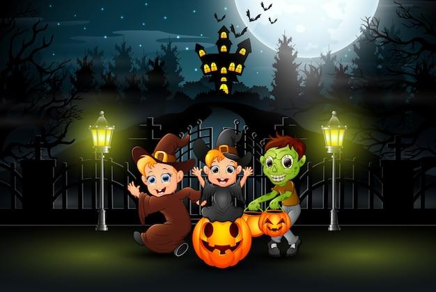 밤에 야외에서 할로윈 의상을 입고 행복한 아이들