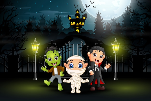 Happy kids wearing halloween costume outdoors at night
