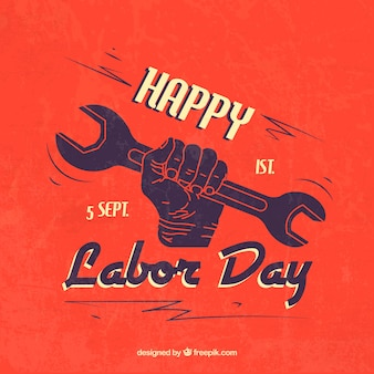 Happy labor day with hand holding a wrench