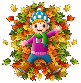 Happy little boy playing with autumn leaves