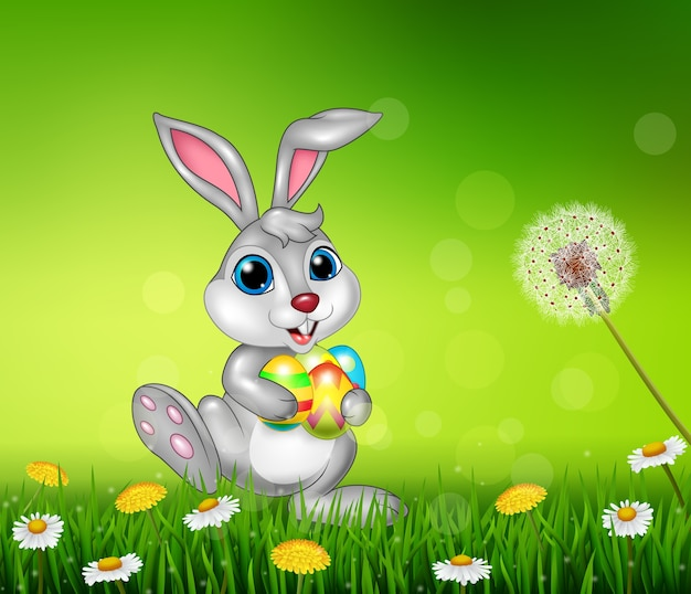 Happy little bunny holding easter eggs on grass background