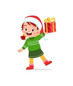 Счастливая маленькая девочка держит подарок на рождество