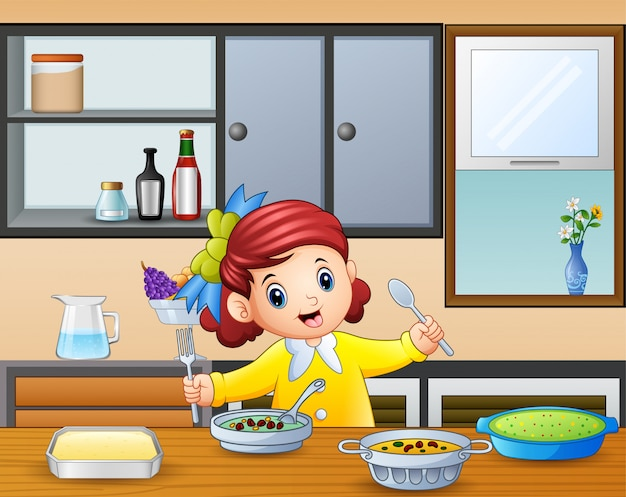 Happy little girl holding spoon and fork eating at the table
