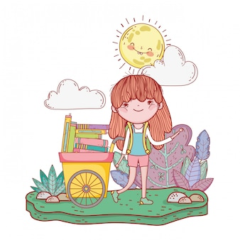 Happy little girl reading books with cart in the field