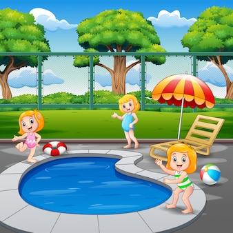 Счастливые маленькие девочки играют в бассейне
