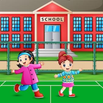 Счастливые маленькие девочки играют на школьной площадке