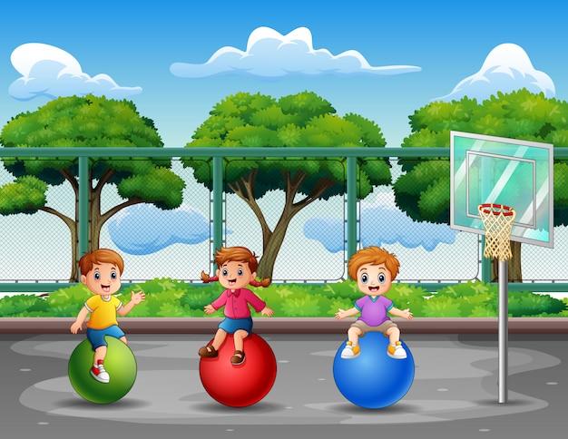 バスケットボールコートで遊んで幸せな小さな子供たち