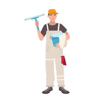 制服を着た幸せな男は、バケツとクリーニングワイパーを立って保持しています。男性のウィンドウクリーナー、白い表面に隔離されたハウスキーピングサービスワーカー