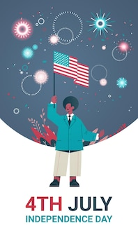 アメリカの独立記念日の休日を祝う米国旗を保持している幸せな男、7月の垂直バナーの4日
