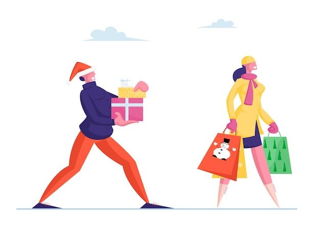 サンタ帽子の幸せな男は弓で包まれたギフトボックスを運ぶ