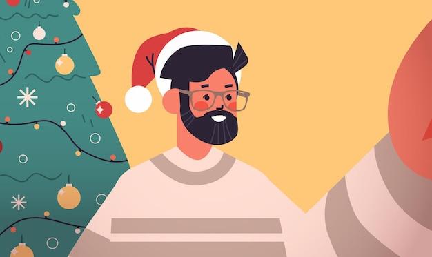 カメラを保持し、モミの木の近くでselfieを撮ってサンタ帽子で幸せな男新年クリスマス休暇お祝いコンセプト横向きの肖像画ベクトル図