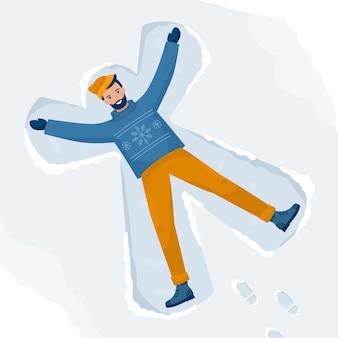 Счастливый человек делает снежных ангелов и лежит на земле