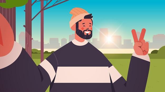 Счастливый человек делает селфи на камеру смартфона парень делает селфи в городском парке городской фон горизонтальный портрет векторная иллюстрация