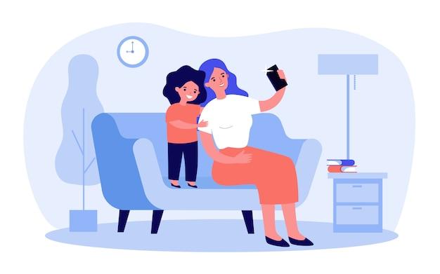 スマートフォンでselfieを取って幸せなママと甘い娘