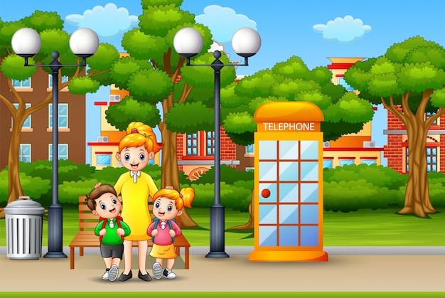幸せな母親と子供たちは都市公園に立っています。