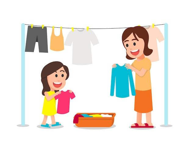 Счастливая мать и дочь вместе сушат одежду