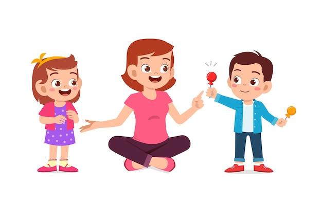 幸せな母親は彼の男の子と女の子の子供にキャンディーとお菓子を与えます