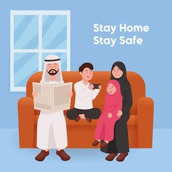 幸せなイスラム教徒の家族が一緒に座って家に滞在します。