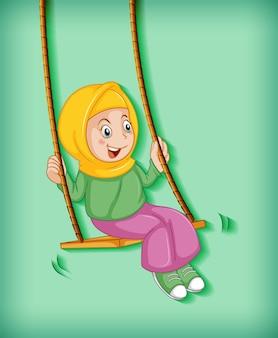 幸せなイスラム教徒の少女がブランコに座る