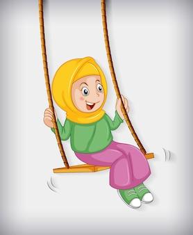 Счастливая мусульманская девушка сидит на качелях