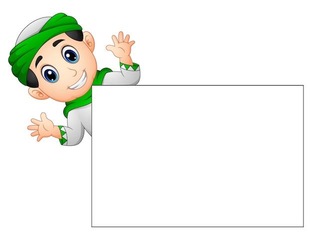 Happy muslim kid waving hand behind blank sign