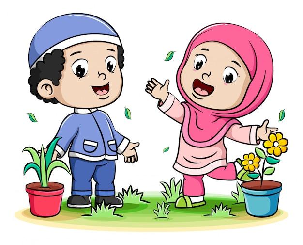Счастливые мусульманские дети играют и цветок в горшке фоне