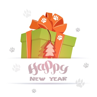Happy new year greeting card big gift box over dog foot prints on background