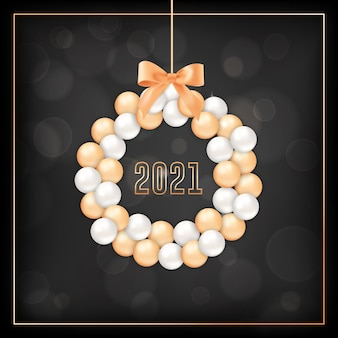 Happy new year greeting card with wreath made of gold and white xmas balls and bow on black blurred background with golden 2021 typography. invitation or elegant new year postcard. vector illustration