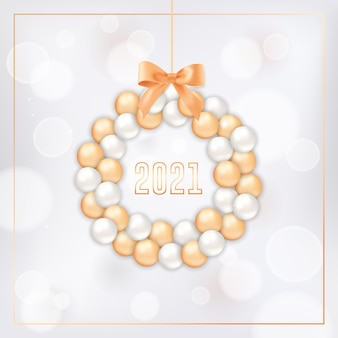 Happy new year greeting card with wreath made of gold and white xmas balls and bow on white blurred background with golden frame and 2021 typography. invitation or brochure, elegant new year postcard