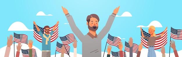 アメリカ独立記念日、7月のバナーの4日を祝う米国の旗を保持している幸せな人々