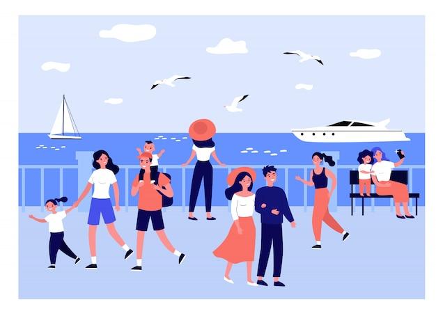 Happy people walking along sea on quay