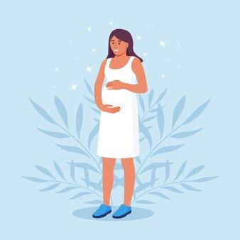 행복한 임신과 모성입니다. 아름 다운 젊은 임신한 여자는 그녀의 배꼽을 보유 하고있다. 엄마는 출산을 기대한다