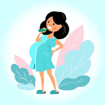 Счастливая беременная девушка в халате ест огурец.