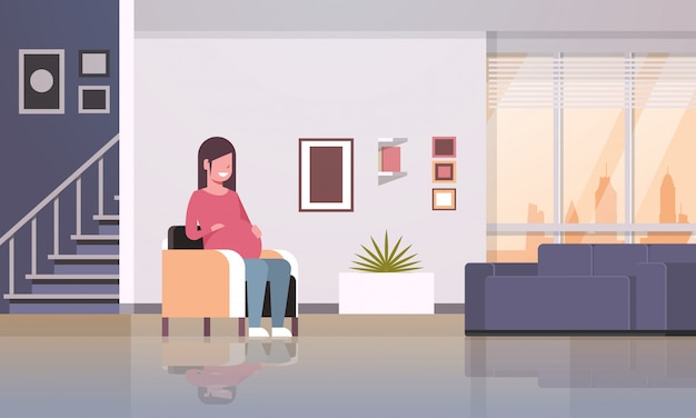Happy pregnant woman sitting in armchair girl