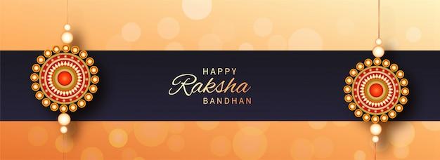 Happy raksha bandhan font with beautiful pearl rakhis (wristband) on purple strip and orange bokeh blur background.