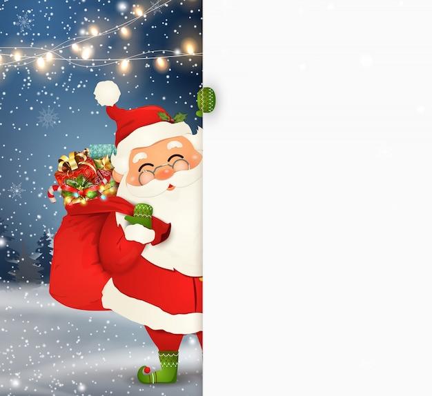 幸せなサンタクロースが空白記号の後ろに立って、大きな空白記号を表示します。ギフト用の箱、白いコピースペースの完全なギフト袋で漫画のサンタクロースのキャラクター。もみ、雪と休日の冬の風景